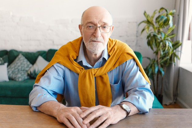 people age lifestyle fashion concept handsome unshaven bald senior man wearing rectangular glasses wrist watch blue shirt yellow sweater sitting wooden desk looking camera 343059 4234